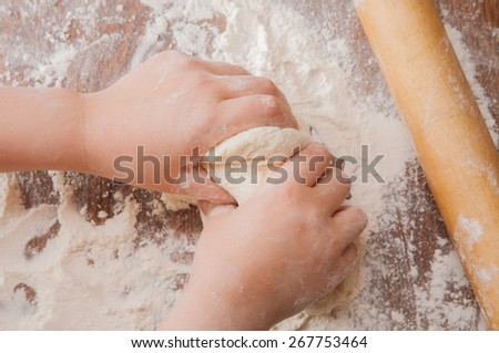 Making pie: kid's hands kneading the dough, rolling-pin and wheat flour on wooden table