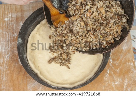 Making pie. Putting filling on raw dough in black metal baking form - stock photo