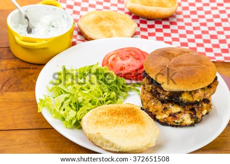 Making Salmon Burgers with salmon patties stuffed with cranberries and gorgonzola cheese. - stock photo