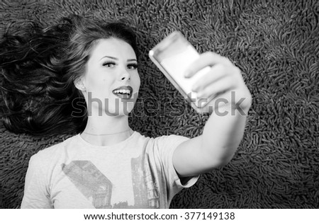 Making self image on mobile phone young beautiful woman relaxing on carpet background. Black and white photography - stock photo