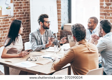 Making serious decisions. Group of young business people discussing something while sitting at the wooden table together      - stock photo