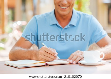 Making some important notes. Close-up of confident mature man writing something in his note pad and smiling while sitting at the table outdoors with house in the background  - stock photo