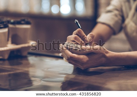 Making some notes. Close-up of woman writing in note pad while standing at bar counter - stock photo