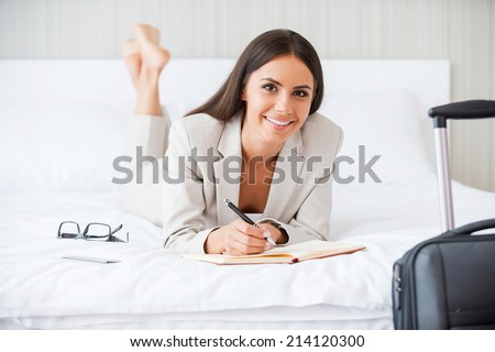Making some urgent notes. Beautiful young businesswoman in suit writing something in her note pad and smiling while lying in the bed at the hotel room  - stock photo