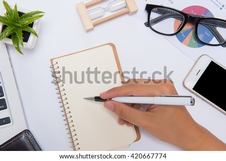 Making some urgent notes. Close-up of man writing something in his note pad while sitting at his working place - stock photo