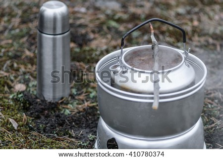 Making soup in the woods with camping stove - stock photo