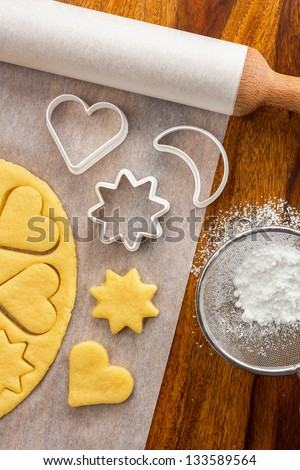 Making sugar cookies with cookie cutters - stock photo