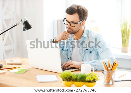 Making sure everything is right. Handsome young man in shirt and eyewear working on laptop while sitting at his working place - stock photo