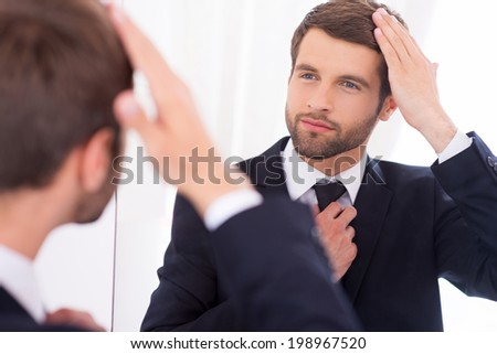 Making sure he looks perfect. Handsome young man in formalwear adjusting his hairstyle and smiling while standing against mirror - stock photo