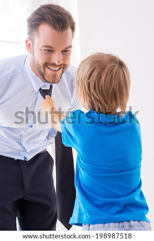 Making sure his father looks good. Playful little boy helping father to tie a necktie  - stock photo