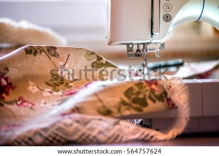 Making table decorations. A shot of a natural beige linen tablecloth, towels and napkins with rose print and a crochet white linen lace trim, being sewed using a sewing machine and needles