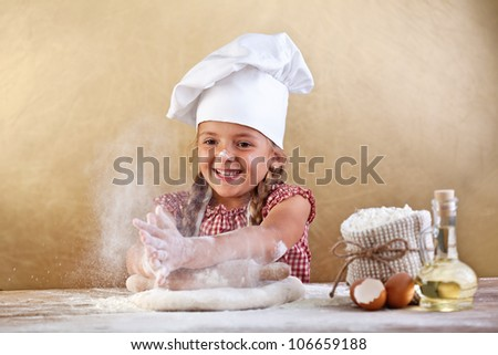 Making the dough for pizza is fun - little chef playing with flour - stock photo