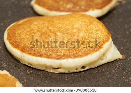 making thick pancakes on dry griddle surface - stock photo