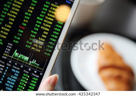 Making trading online on the tablet with business woman hand and croissant
