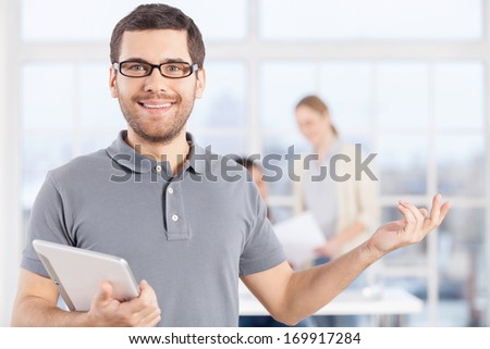 Making your business easy. Cheerful young businessman in casual wear holding digital tablet and smiling while his colleagues communicating on the background - stock photo