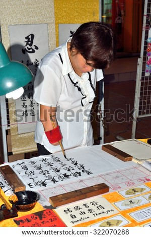 MALACCA, MALAYSIA - AUG 7, 2015: An unidentified handicap woman's hand writing chinese calligraphy at Jonker Street to earn a living for her family on 7 August, 2015 in in Malacca, Malaysia.  - stock photo