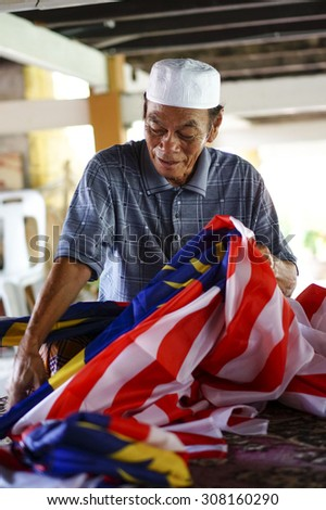 MALACCA, MALAYSIA - AUGUST 23rd : Unidentified elderly preparing Malaysian flag for the Independence day Aug 23, 2014 in Malacca, Malaysia. - stock photo