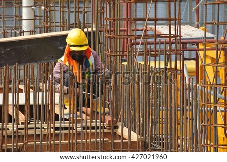 MALACCA, MALAYSIA -MARCH 30, 2016: Construction workers fabricating steel reinforcement bar at the construction site in Malacca, Malaysia. The reinforcement bar was ties together using tiny wire.  - stock photo
