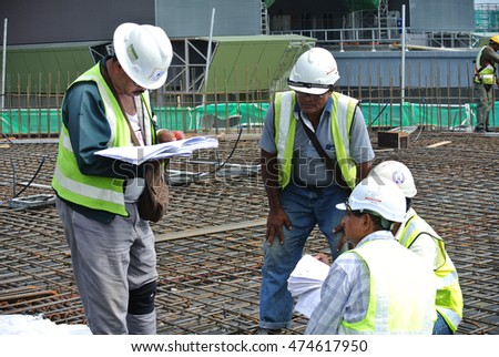 MALACCA, MALAYSIA -MAY 4, 2016: Construction workers discussing and holding construction drawings at construction sites.