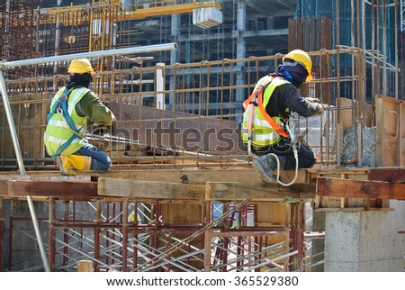 MALACCA, MALAYSIA â?? NOVEMBER 03, 2015: Construction workers fabricating high level beam steel reinforcement bar at the construction site in Malacca, Malaysia  - stock photo
