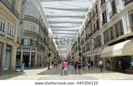 MALAGA, ANDALUCIA, SPAIN - JUNE 29, 2016: Shoppers under canopy covered pedestrian shopping street in Malaga city centre.