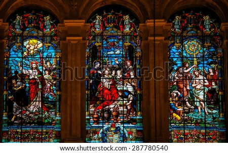 MALAGA, SPAIN - NOVEMBER 29, 2013: Stained glass window depicting Jesus casting away Lucifer, the Wedding at Cana and the baptism in the River Jordan by Saint John, in the cathedral of Malaga, Spain. - stock photo