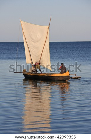 Malagasy fishermen and their outrigger canoes pirogue some of which had makeshift sails - stock photo