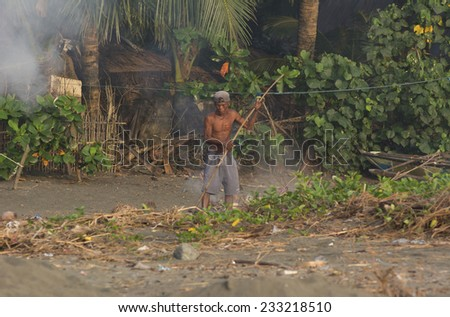 Malandog, Philippines - October 20, 2014: Filipino man cleaning the dirty beach and burning the waste  - stock photo