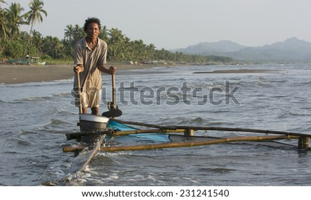 Malandog, Philippines - October 22, 2014: Man catching Milkfish fry (bangus) to sell to the milkfish farms in the province of Antique - stock photo