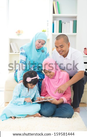 malay indonesian family surfing internet at home.  - stock photo