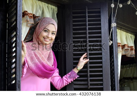 Malay muslim woman open a traditional window