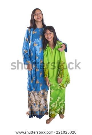 Malay teenage sisters in traditional attire over white background