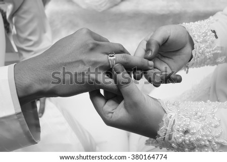 Malay wedding groom bolstering silver ring on bride's finger.black and white - stock photo