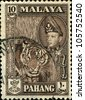 MALAYA - CIRCA 1957-61: A stamp printed in state of Pahang in the East Coast Region of Malaya shows tiger and Sultan Abu Bakar, series, circa 1957-61 - stock photo