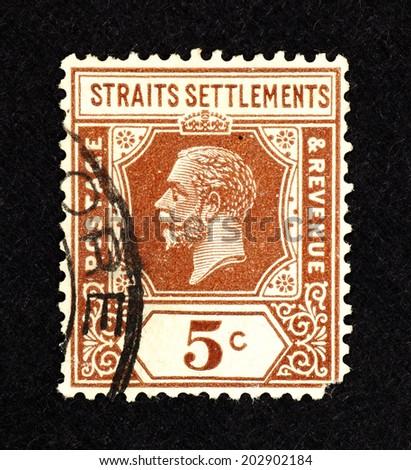 MALAYA - CIRCA 1921: Brown color postage and revenue stamp printed in Malaya for the Malayan Straits Settlements with portrait image of King George V. - stock photo