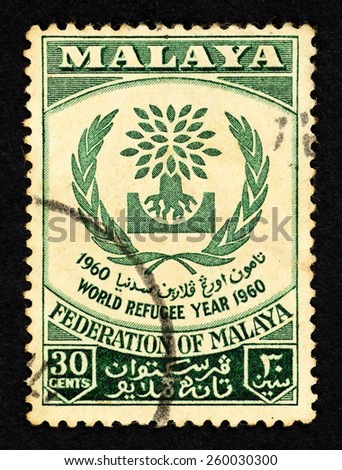 MALAYA - CIRCA 1960: Green color postage stamp printed in Federation of Malaya with image of the World Refugee symbol to commemorate World Refugee Year 1960. - stock photo