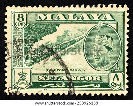 MALAYA - CIRCA 1957: Green color postage stamp printed in Selangor (Federation of Malaya) with illustrative image of the East Coast Railway and portrait of Sultan Hisamuddin Alam Shah.  - stock photo