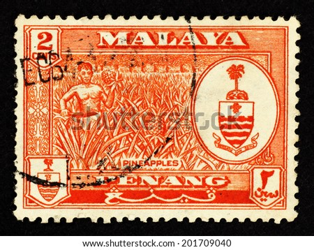 MALAYA - CIRCA 1957: Orange color postage stamp printed in Malaya Penang with image of a farmer in a pineapple plantation.  - stock photo
