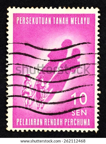 MALAYA - CIRCA 1965: Pink color postage stamp printed in Federation of Malaya with illustrative image of school children with long shadow to commemorate free primary school education. - stock photo