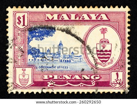 MALAYA - CIRCA 1957: Red color postage stamp printed in Penang (Federation of Malaya) with illustrative image of government offices and the Penang state crest. - stock photo