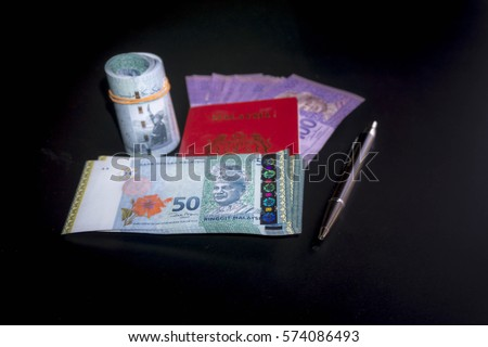 Malaysia bank notes and Malaysia Passport isolated with Black background.