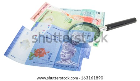 Malaysia bank notes money with magnifying glass - stock photo