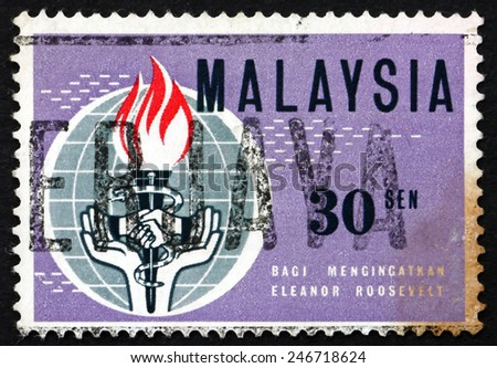 MALAYSIA - CIRCA 1964: a stamp printed in Malaysia shows Globe, Torch, Snake and Hands, Eleanor Roosevelt, circa 1964 - stock photo