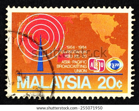 MALAYSIA - CIRCA 1984: Brown color postage stamp printed in Malaysia with image of world map and icon of broadcast antennae to commemorate the 20th anniversary of Asia Pacific Broadcasting Union(ABU). - stock photo