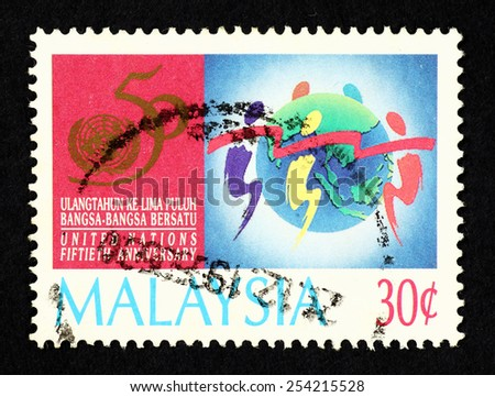 MALAYSIA - CIRCA 1995: Colorful postage stamp printed in Malaysia with caricature image of people around a globe to commemorate the 50th Anniversary of the Signing of the United Nations Charter. - stock photo