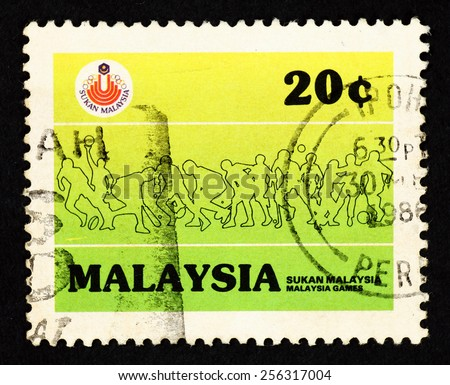 MALAYSIA - CIRCA 1986: Green color postage stamp printed in Malaysia with silhouette image of sportsman to commemorate the bi-annual Malaysia Games. - stock photo