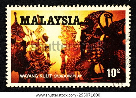 MALAYSIA - CIRCA 1982: Orange color postage stamp printed in Malaysia with image of he Malay traditional cultural puppet shadow play art known as Wayang Kulit. - stock photo