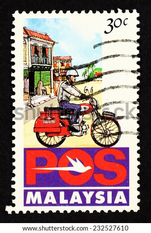 MALAYSIA - CIRCA 1992: Postage stamp printed in Malaysia with caricature image of Pos Malaysia postman on a postal delivery motorcycle. - stock photo