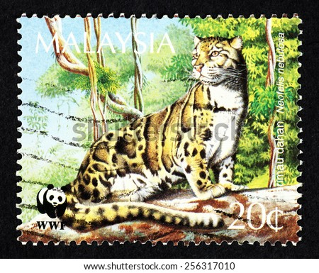 MALAYSIA - CIRCA 1995: Postage stamp printed in Malaysia with image of a Clouded leopard (Neofelis nebulosa) in a jungle environment. - stock photo