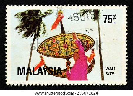 MALAYSIA - CIRCA 1982: Postage stamp printed in Malaysia with image of a Malay native man with a traditional kite known as Wau. - stock photo